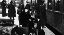 """_Judenverfolgung:_Auswanderung_deutscher_Juden._–_Jüdische_Familie_am_Bahnsteig_kurz_vor_der_Abreise_(organisiert_vom_Hilfsverein_der_Deutschen_Juden);_die_Aufnahme_ist_beschriftet_mit_den_Worten_""""Wir_warten""""._Foto,_Berlin,_um_1937_(Abraham_Pisarek)."""