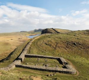 Milecastle_39,_Castle_Nick,_near_Steel_Rigg_on_Hadrian's_Wall,_with_Crag_Lough_in_the_distance,_Northumberland,_England._Hadrian's_Wall_was_built_73_miles_across_Britannia,_now_England,_122-128_AD,_under_the_reign_of_Emperor_Hadrian,_ruled_117-138,_to_mar