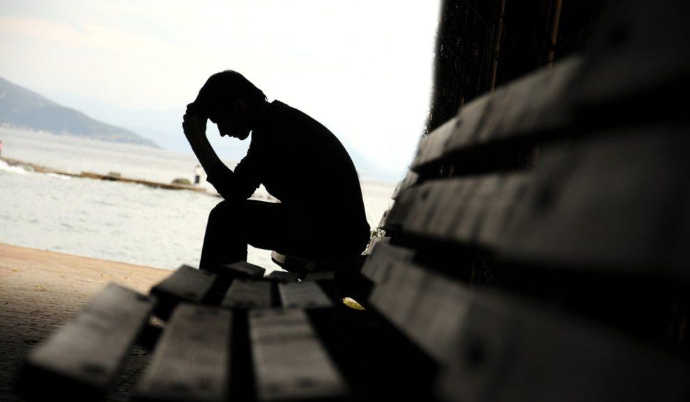 Deprimierter Mann auf Sitzbank am Strand