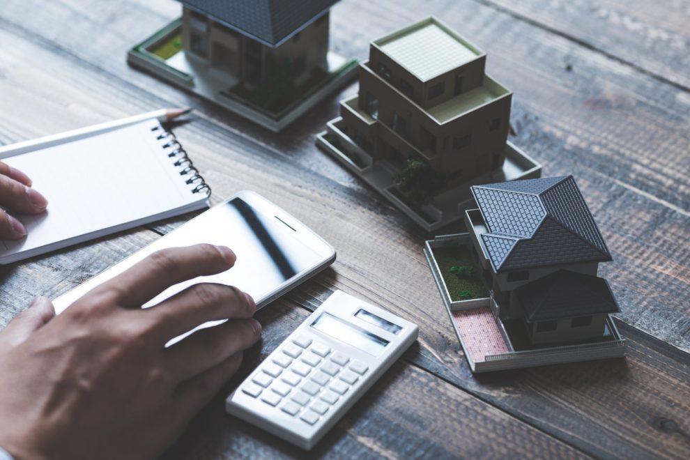 Schreintisch mit Tischrechner, Schreibutensilien und Hausmodell