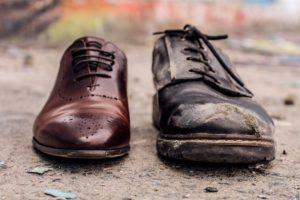 Neuer, hochwertiger Schuh neben altem, dreckigem Schuh